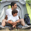 Father and son sitting outside a tent — Stock fotografie