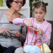 Grandmother teaching a little girl to knit — Stock Photo
