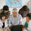 Teacher and a group of pupils sitting round a laptop — Stock Photo