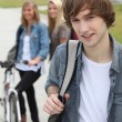 Stock Photo: Three teenagers arriving at college