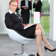 Stock Photo: Businesswoman sat in chair with colleagues in background