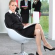 Businesswoman sat in chair with colleagues in background — Stock Photo