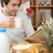 Foto Stock: Couple reading the newspaper over breakfast