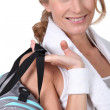 Woman post-workout with a gym bag and towel round her neck — Stock Photo