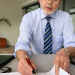 Stock Photo: Senior businessman filling in diary