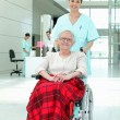 Hospital nurse pushing an elderly lady in a wheelchair — Stock Photo
