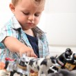 Royalty-Free Stock Photo: Young boy playing with a selection of toy figurines and animals