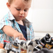 Young boy playing with a selection of toy figurines and animals — Stock Photo