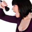 Woman singing into a make-up brush — Stock Photo