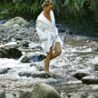 Stock Photo: Womin white bathing gown walking down stream