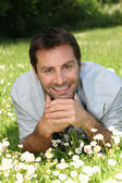 Man lying in a field of daisies — Stock Photo
