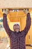 Muž pomocí vodováhou zkontrolovat dřeva — Stock fotografie