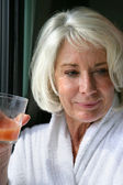 Oudere dame vruchtensap drinken — Stockfoto