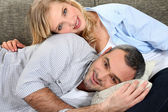 Sweet couple embracing on the couch — Stock Photo