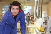Apprentice working in a factory — Stock Photo