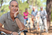 Senior on a bike with friends in the background — Stock Photo