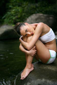 Model sat on rock in stream — Stockfoto
