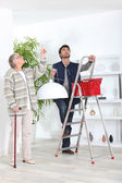 Man fitting ceiling light for old lady — Stok fotoğraf