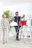 Man montage plafondlamp voor oude dame — Stockfoto