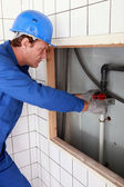 Plumber tightening a pipe — Stock Photo
