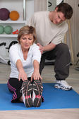 Mature woman sitting on an exercise mat with a personal trainer — Stock Photo