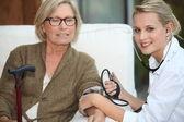 En läkare som tar hennes patientens blodtryck. — Stockfoto