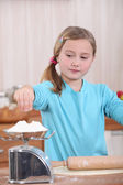 Child weighing flour on a scale — Stock Photo
