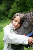 Child stroking horse — Stock Photo
