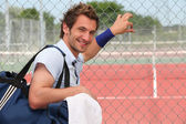 Tennis player leaning against fence — Stock Photo