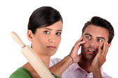 Angry woman threatening man with rolling pin — Stock Photo