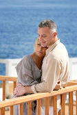 Middle aged couple stood on balcony overlooking the sea — Stock Photo