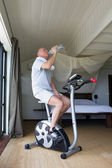 Man cycling on machine at home — Stock Photo