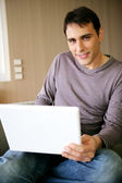 Man sat at home with a laptop — Stock Photo