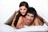 Young couple naked in bed — Stock Photo