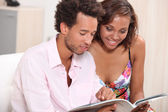 Young couple browsing through magazine — Stock Photo