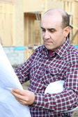 Housebuilder looking at plans on site — Stock Photo