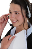 Smiling woman wearing a headset and holding a notebook — Stock Photo