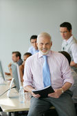 Senior manager sitting on a desk in front of his team — Stockfoto