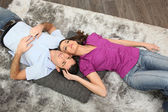 Woman cuddling man laid on a carpet — Stock Photo
