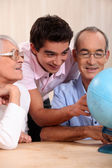 Grandparents ant their grandson looking at a globe — Stock Photo