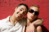 Cool couple posing against a red wall — Stock Photo