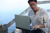 Man using a laptop computer by the water — Stock Photo