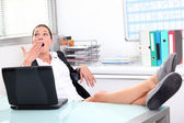 Young woman yawning in front of laptop — Stock Photo