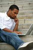 Portrait of a young man sitting in front of a laptop computer — Stock Photo