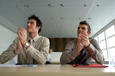 Businessmen sat at their desks applauding — Stock Photo