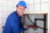 Plumber installing pipes with a large wrench — Stock Photo