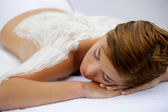 Young woman laid with cream on her back — Stock Photo