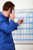 Manual worker writing names onto a wall planner — Stock Photo