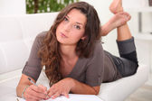 Young woman lying on a sofa writing in a journal — Foto Stock