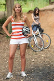 Two young women reposing near mountain bikes — Stock Photo